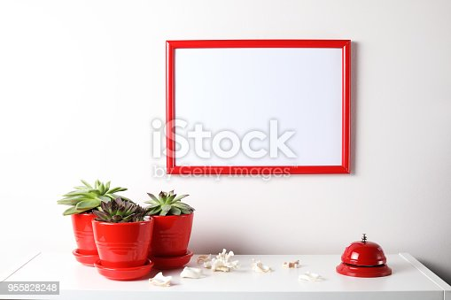 518847146istockphoto Red and white frame poster with plant in pot on table. 955828248