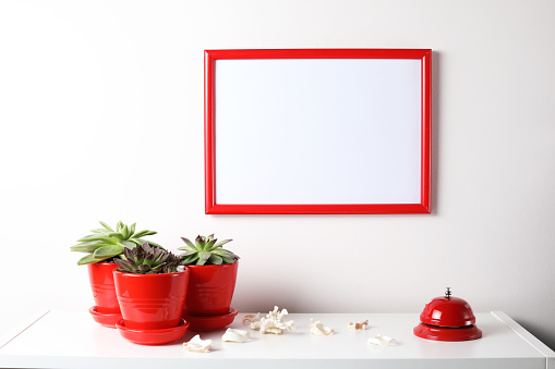 518847146 istock photo Red and white frame poster with plant in pot on table. 955828248