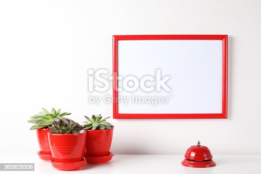 518847146istockphoto Red and white frame poster with plant in pot on table. 955828306