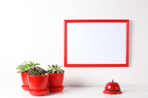 518847146 istock photo Red and white frame poster with plant in pot on table. 955828306