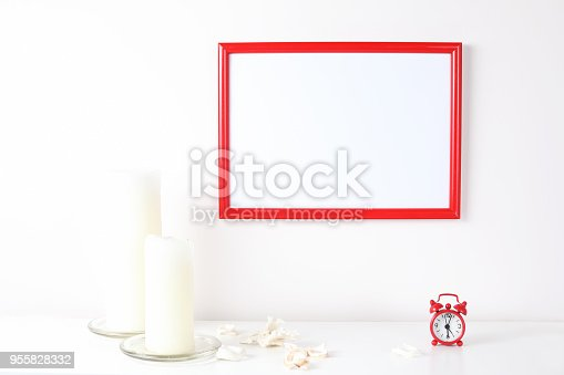 518847146istockphoto Red and white frame poster with plant in pot on table. 955828332
