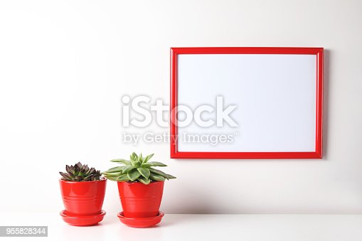 518847146istockphoto Red and white frame poster with plant in pot on table. 955828344