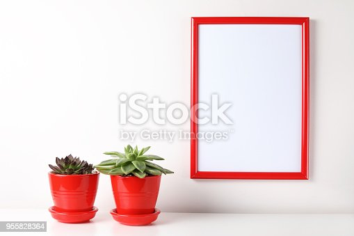 518847146istockphoto Red and white frame poster with plant in pot on table. 955828364