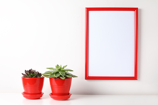 518847146 istock photo Red and white frame poster with plant in pot on table. 955828364