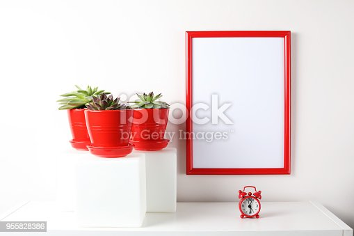 518847146istockphoto Red and white frame poster with plant in pot on table. 955828386