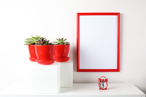 518847146 istock photo Red and white frame poster with plant in pot on table. 955828386