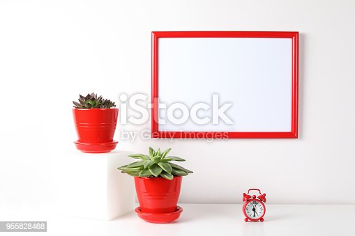 518847146istockphoto Red and white frame poster with plant in pot on table. 955828468