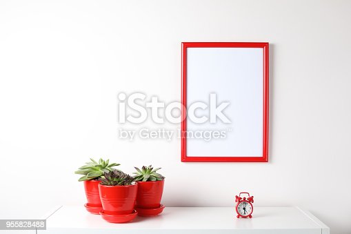 518847146istockphoto Red and white frame poster with plant in pot on table. 955828488