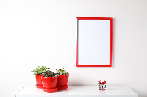 518847146 istock photo Red and white frame poster with plant in pot on table. 955828488