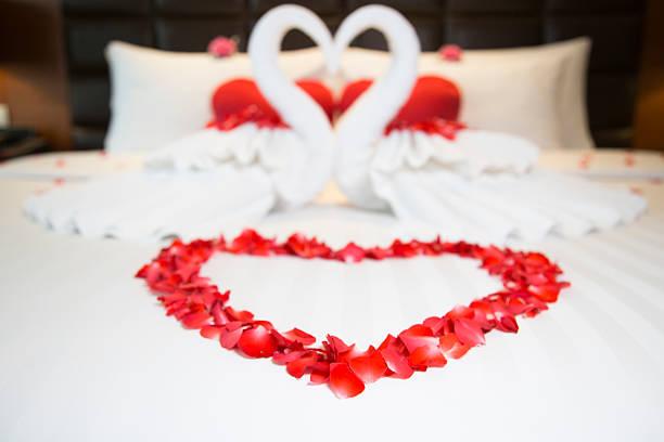 schlafzimmer im romantischen hotel suite mit herzförmigen dekoration - hochzeitsreise ohne mann stock-fotos und bilder