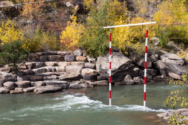 Red and white kayak slalom hanging over the Animas river Durango whitewater park on the Animas river animas river stock pictures, royalty-free photos & images