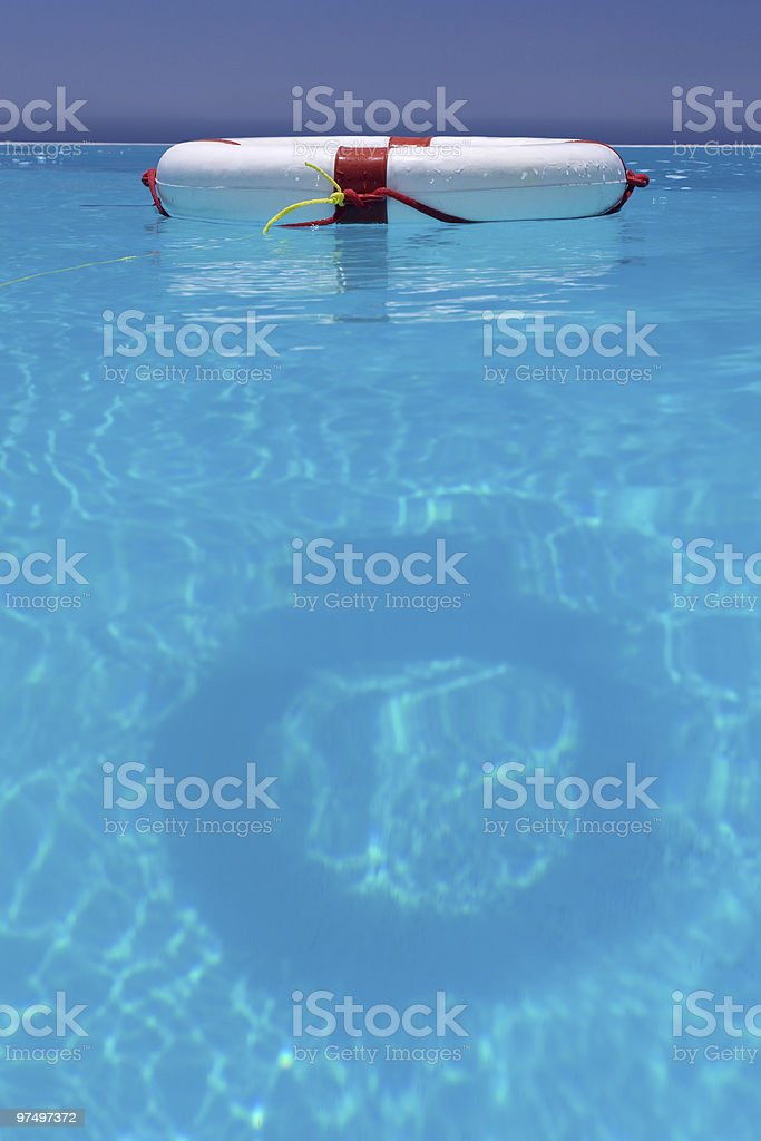 A red and white lifesaver floating in a swimming pool royalty-free stock photo