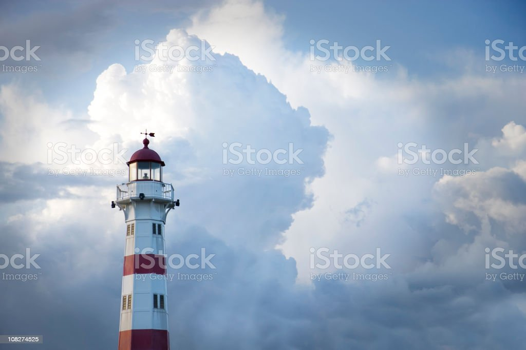 Red and white lighthouse against cloudy blue sky royalty-free stock photo