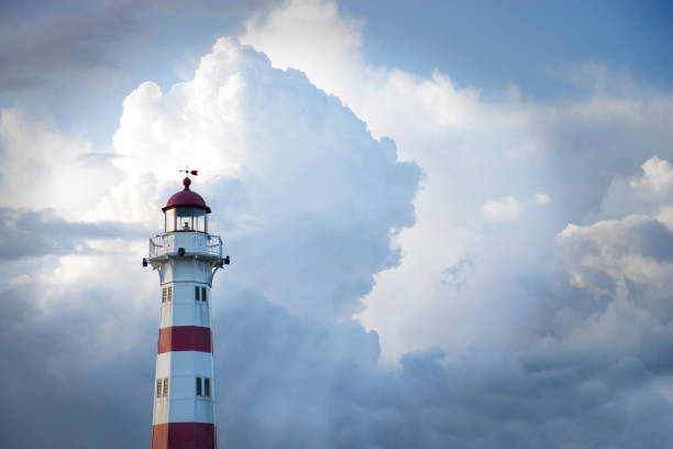 Red and white lighthouse against cloudy blue sky stock photo
