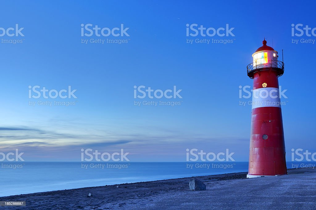 Red and white lighthouse and a clear sky at dusk - Royalty-free Beach Stock Photo