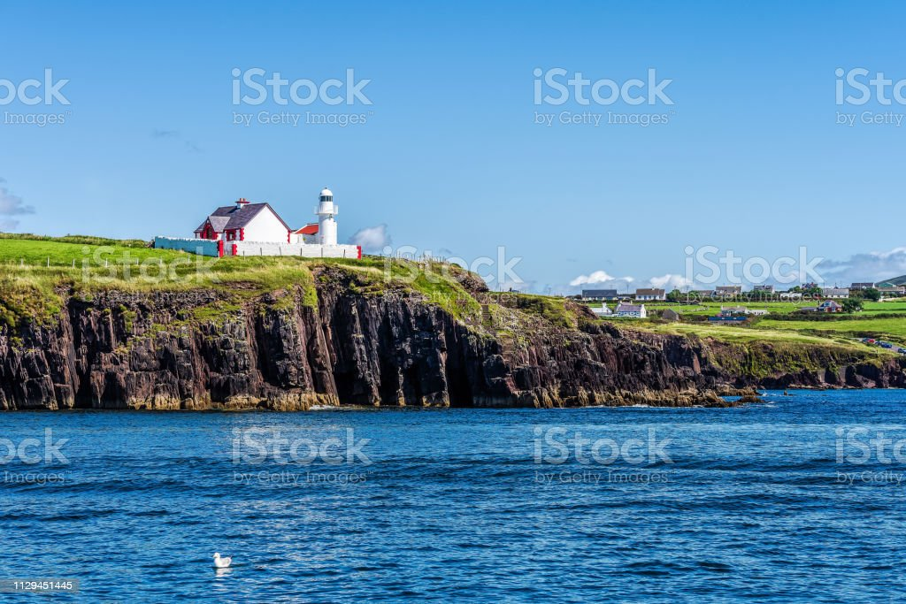 Red And White Lighthouse On Cliff With Village In A Distance