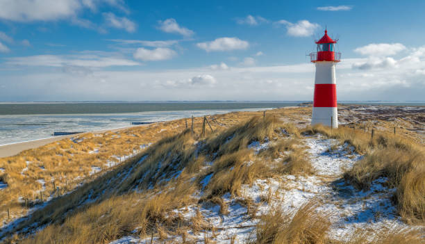 Red and white Lighthouse on sand dune in snow, Island Sylt, Germany stock photo