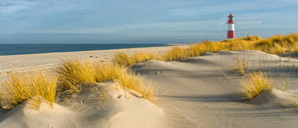 Red and white Lighthouse on sand dunes, Island Sylt, Germany stock photo