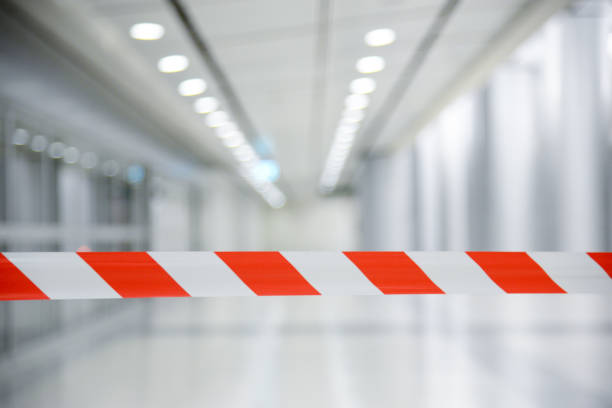 Red and White Lines of barrier tape. At subway station of airport background.Red White warning tape pole fencing is protects for No entry stock photo