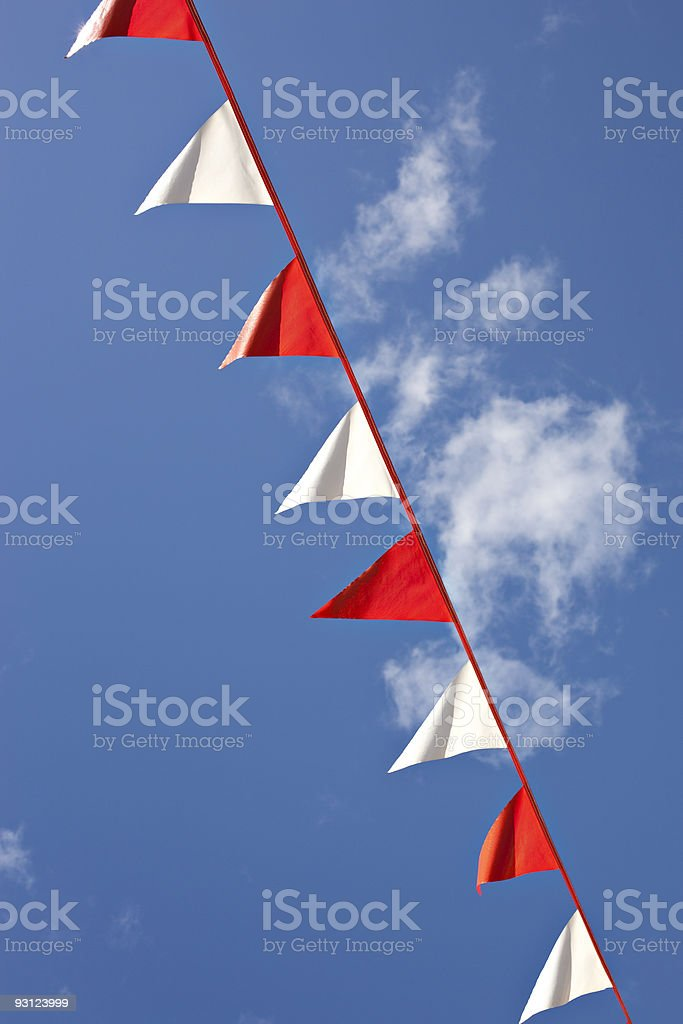 Red and White Pennants against a blue sky stock photo