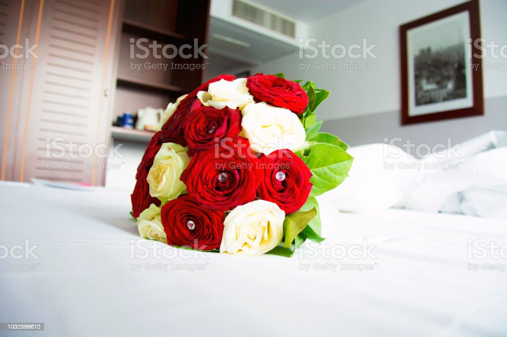 Red and White Roses Bouquet on a Bed in Isolated Color stock photo