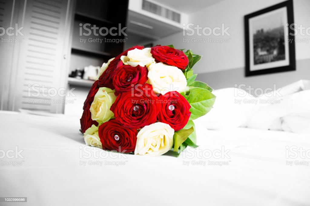 Red and White Roses Bouquet on a Bed stock photo