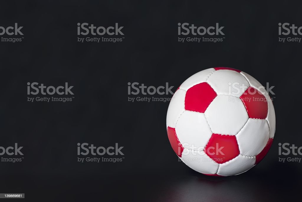 Red and white soccer ball on a black background royalty-free stock photo