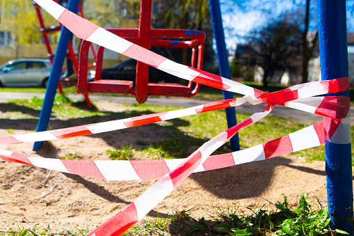 Red and white stripe barrier tape around playground. Fencing red and white tape, warning tape.