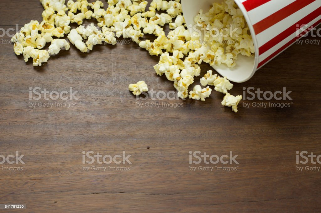 Red and white striped  box of popcorn for movie on wooden background ,Popcorn frame on wooden background stock photo