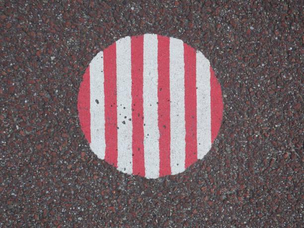 rode en witte gestreepte cirkel op een rode asfaltweg foto