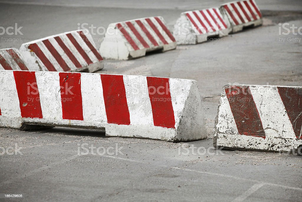 Red and white striped concrete road barriers stock photo