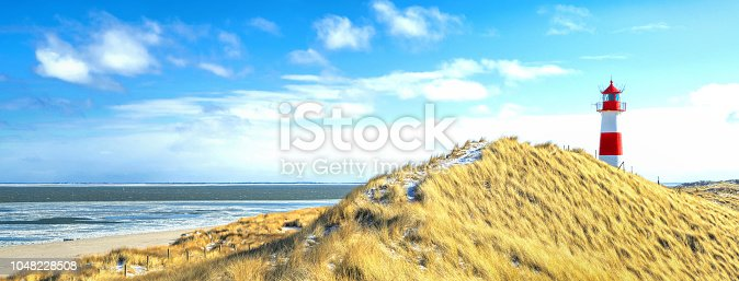 Red and white striped lighthouse on sand dunes of island Sylt in winter sunlight.