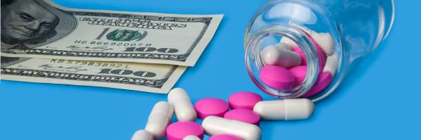 rote und weiße tabletten verstreut aus einer glasflasche auf blauem grund. - geld schön verpacken stock-fotos und bilder