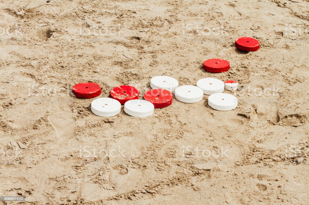 Red and white tejo discs game on beach sand stock photo