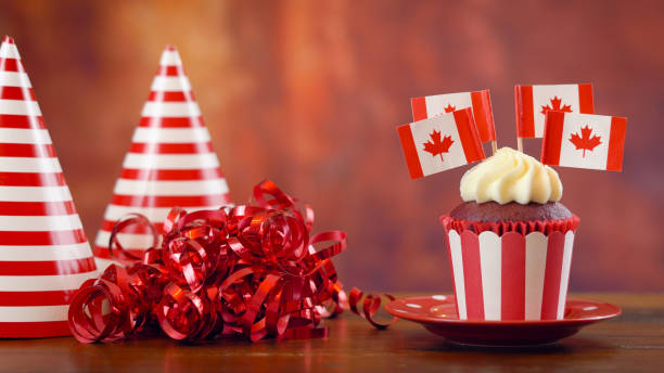 red and white theme cupcakes with canadian maple leaf flags - canada day stock pictures, royalty-free photos & images