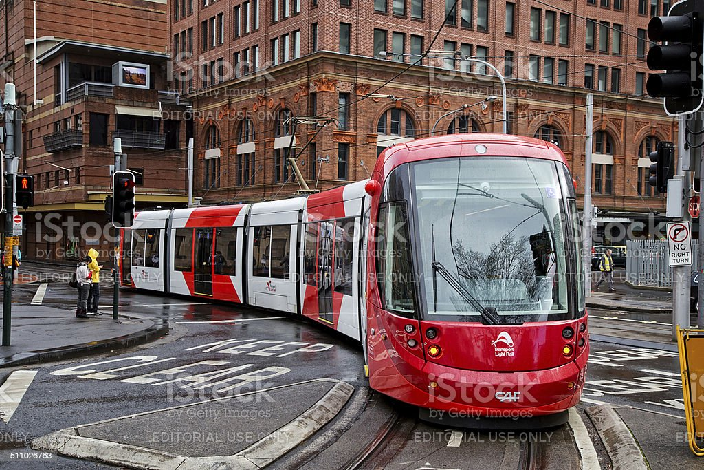 Red and white tram travels along a street in Sydney stock photo