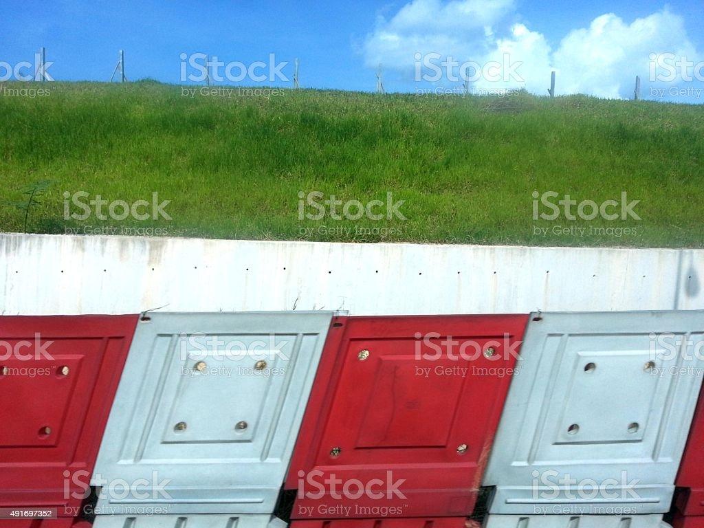 Rote und weiße Mauer und grünem Gras und blauer Himmel. – Foto