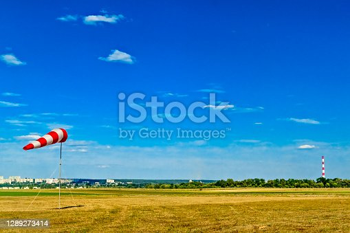 Red and white windsock wind sock on blue sky, green field and clouds background on aerodrome or airdrome. Shows wind speed and direction.