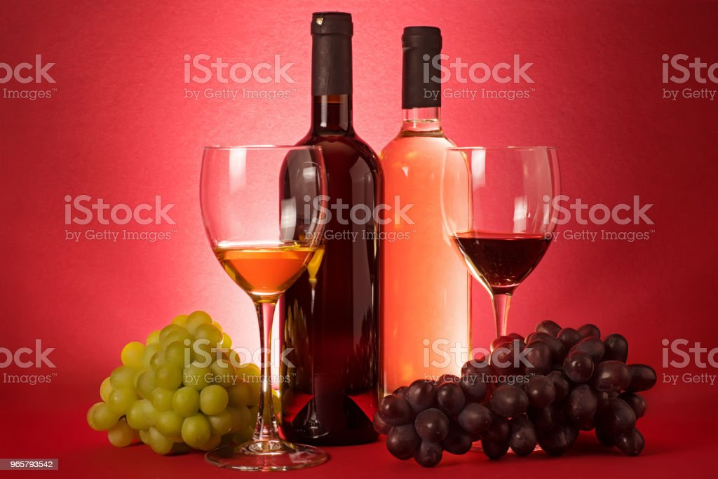 Composition with red and white wine bottles, grape an drinking...