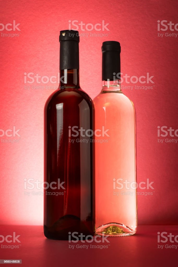 Red and white wine bottles on red background