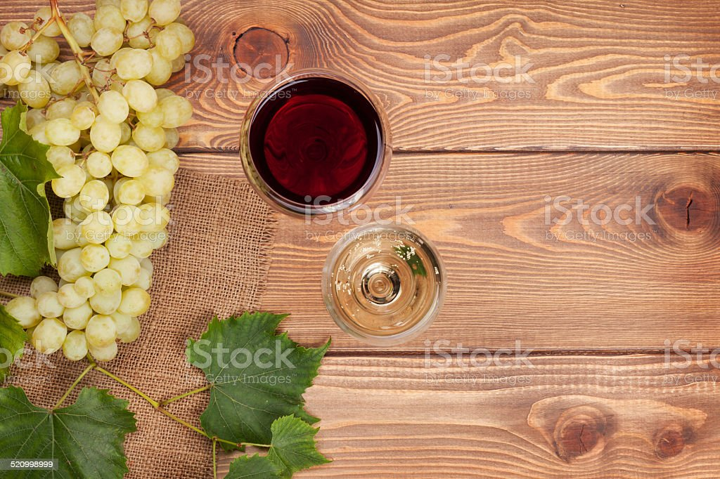 Red and white wine glasses and bunch of grapes stock photo