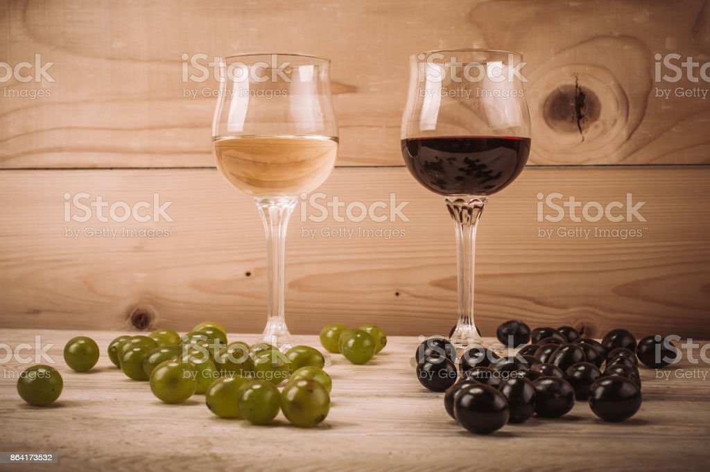 Red and white wine glasses and grape on wooden table royalty-free stock photo