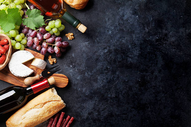 Red and white wine, grape, cheese and sausages stock photo