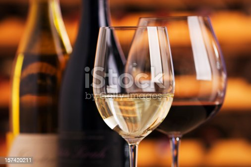 Wineglasses and wine bottles on display for serving a wine tasting. Red and white fermented grape beverages are poured into two sparkling glasses. Warm, orange brown wooden cellar wine racks are reflected and in soft focus in the background. The close-up view of the alcohol is indoors, with no people.
