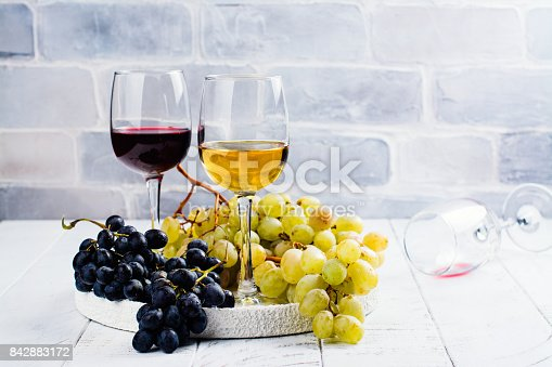 924487256 istock photo Red and white wine in glasses with grapes 842883172