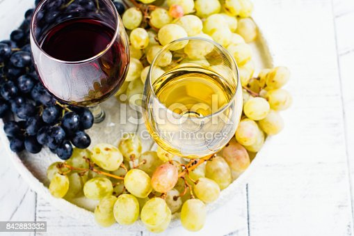 924487256 istock photo Red and white wine in glasses with grapes 842883332