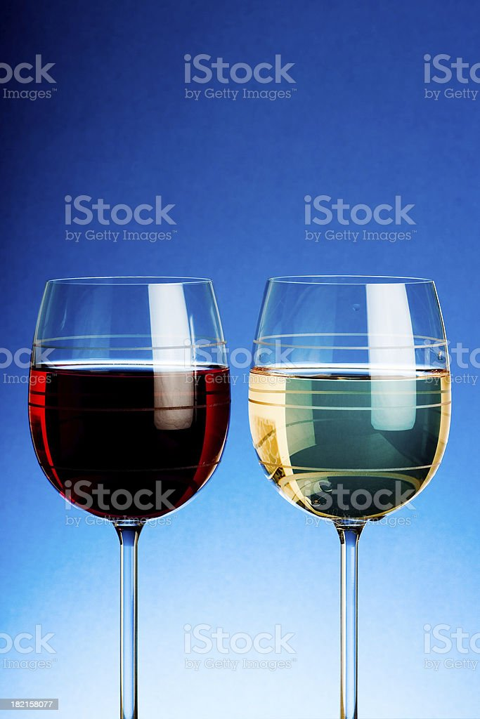 Red and White wine in wineglasses on blue background royalty-free stock photo