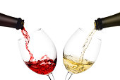 istock red and white wine poured from a bottle into wine glass on white background, isolated 1025274216