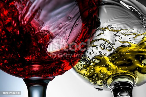 Red and white wine splash in wineglasses close-up macro.