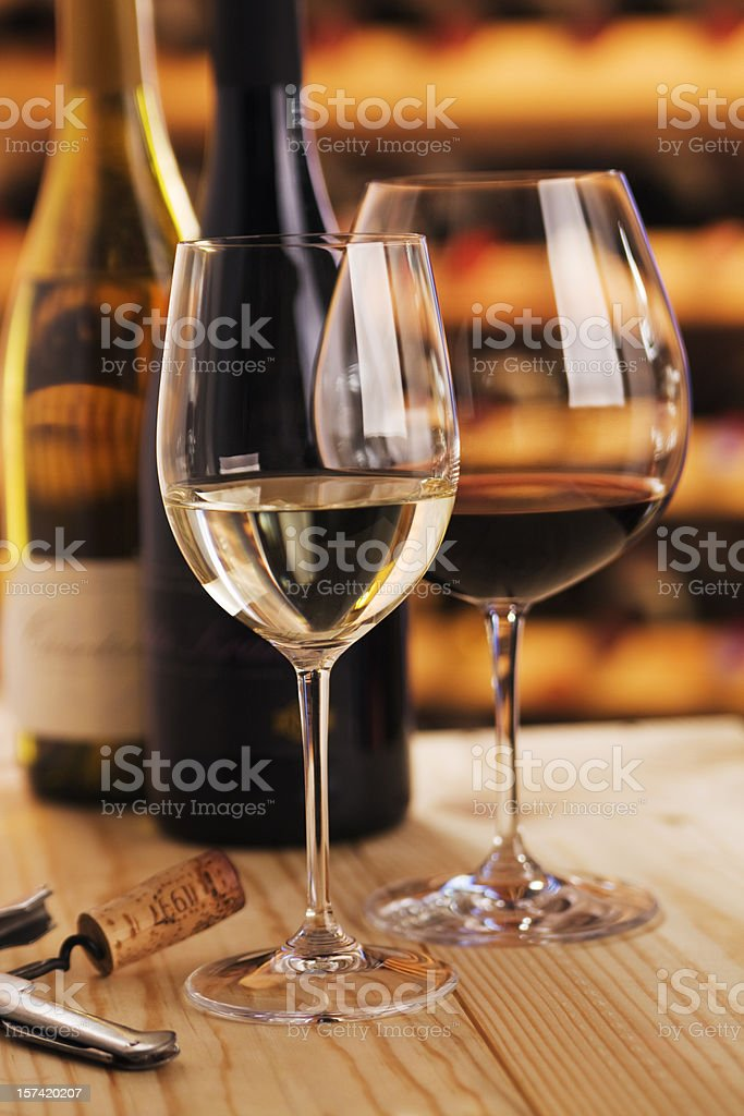 Red and White Wine Tasting Glasses with Corkscrew in Cellar stock photo